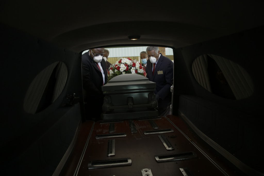 FILE - In this April 18, 2020 file photo, mortician Cordarial O. Holloway, foreground left, funeral director Robert L. Albritten, foreground right, an...