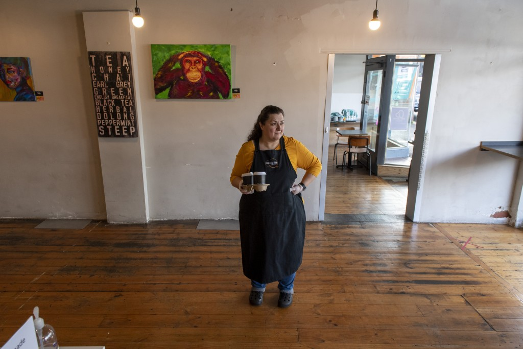 Cafe owner Maria Iatrou stands at her empty coffee shop in Melbourne, Monday, July 6, 2020. As Australia is emerging from pandemic restrictions, the V...