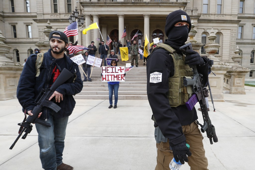 FILE - In this Wednesday, April 15, 2020 file photo, protesters carry rifles near the steps of the Michigan State Capitol building in Lansing, Mich. F...