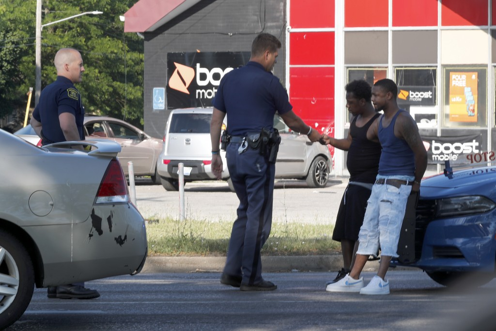 Michigan State Troopers talk with two Black men Monday, June 29, 2020, during a stop on the impoverished east side of Saginaw, Mich. Black residents h...