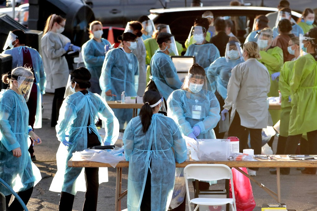 FILE - In this June 27, 2020, file photo, medical personnel prepare to test hundreds of people lined up in vehicles in Phoenix's western neighborhood ...