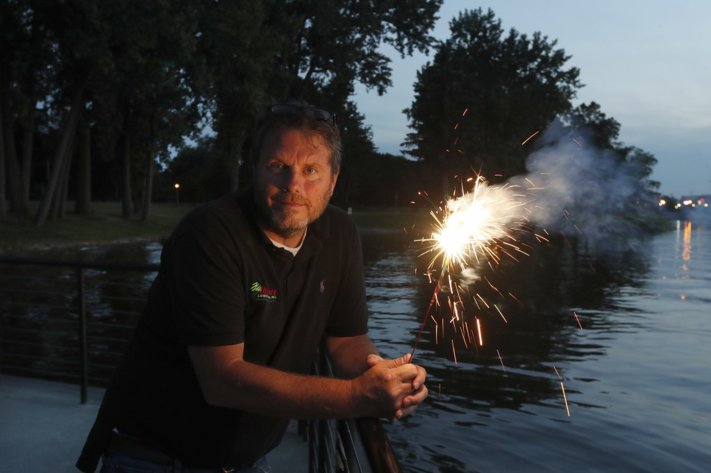 Local landscaper and chairman of Saginaw Area Fireworks, Tom Roy, holds a sparkler as he poses for a portrait Monday, June 29, 2020, in Rust Park on O...