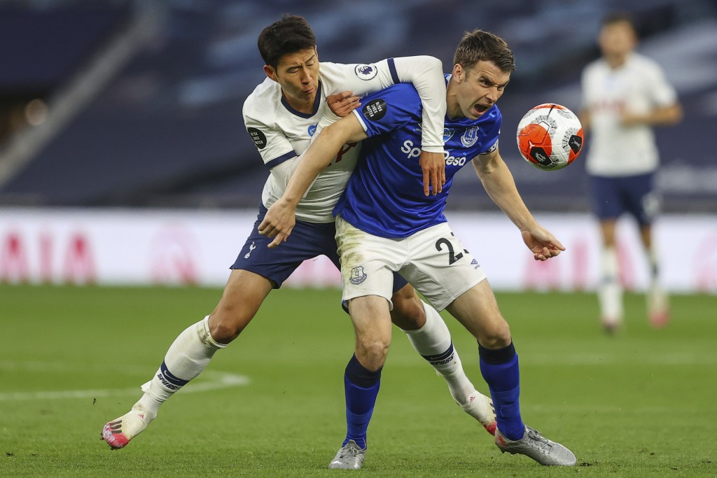 Tottenham's Son Heung-min, left, duels for the ball with Everton's Seamus Coleman during the English Premier League soccer match between Tottenham Hot...