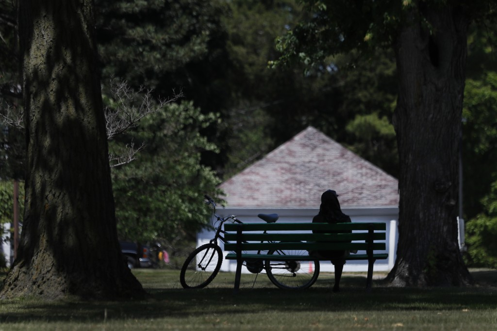 A cyclist sits on a Hoyt Park bench Monday, June 29, 2020, in Saginaw, Mich. The county is majority-white and one-fifth the population is Black. (AP P...