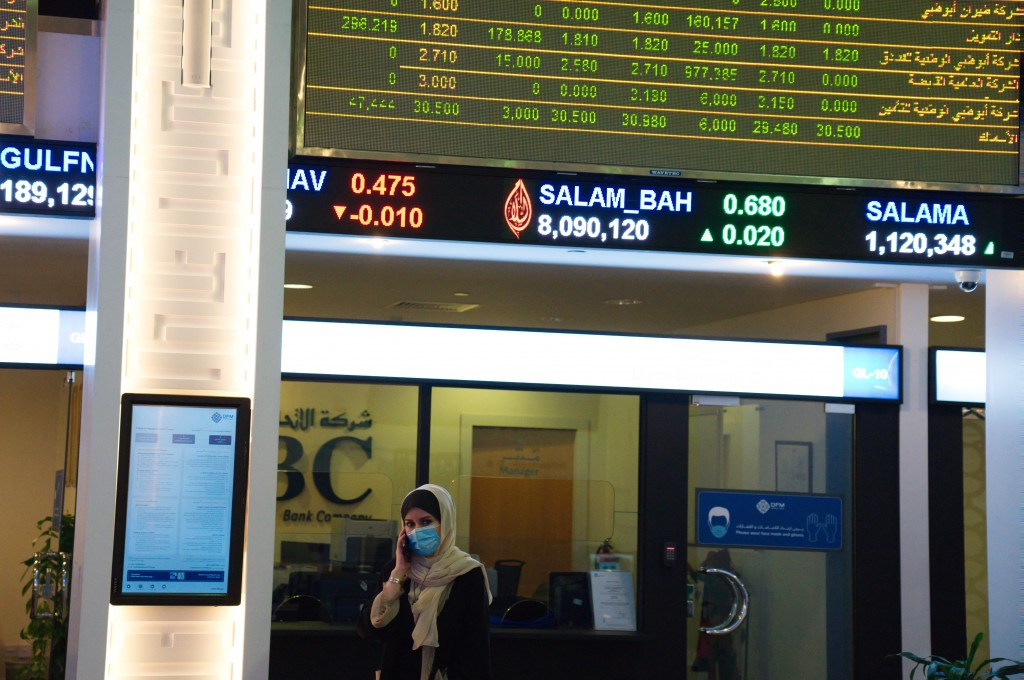A woman wearing a face mask due to the coronavirus pandemic talks on the phone on the floor of the Dubai Financial Market in Dubai, United Arab Emirat...