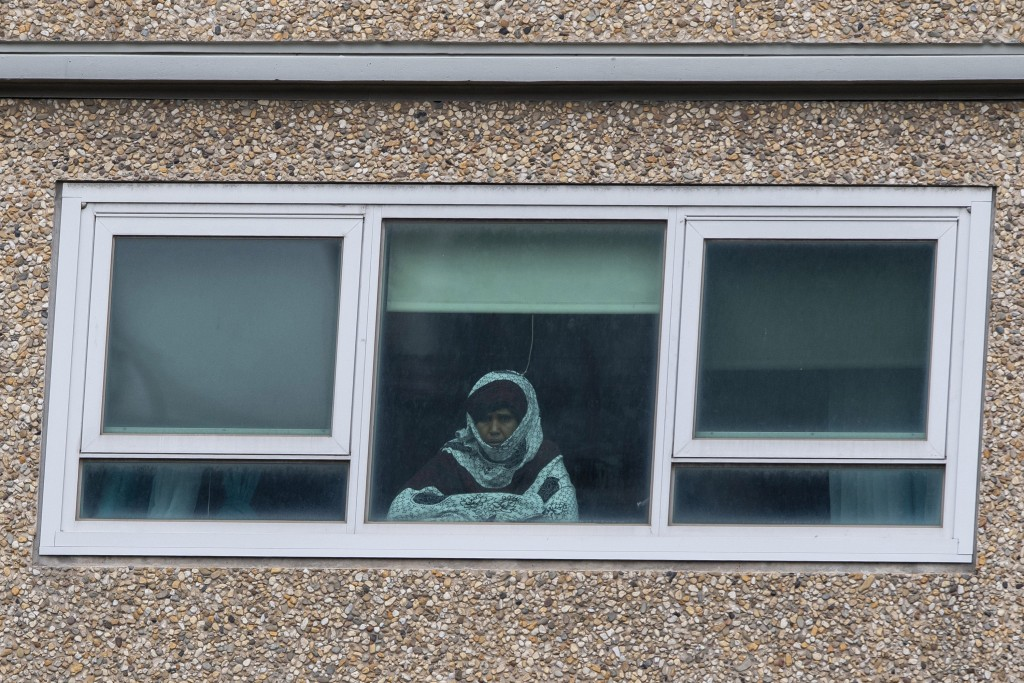 A woman looks out a window from a locked-down public housing tower in Melbourne, Monday, July 6, 2020. As Australia is emerging from pandemic restrict...