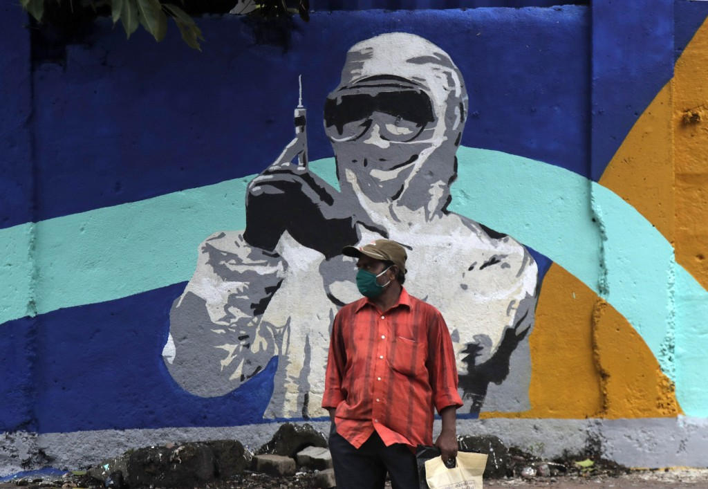 A man stands in front of a graffiti honoring those in the frontlines in the fight against the coronavirus in Mumbai, India, Tuesday, July 7, 2020.  In...