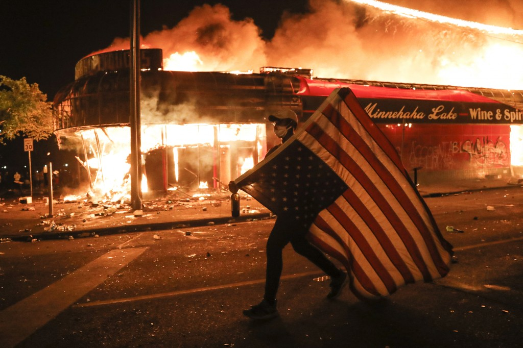 FILE - In this early Friday, May 29, 2020 file photo, a protester carries a U.S. flag upside, a sign of distress, next to a burning building in Minnea...