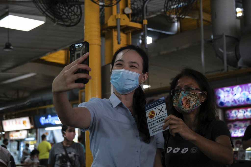 Workers' Party candidate Nicole Seah takes a selfie with a female supporter at Bedok South market during the final day of the election campaign Wednes...