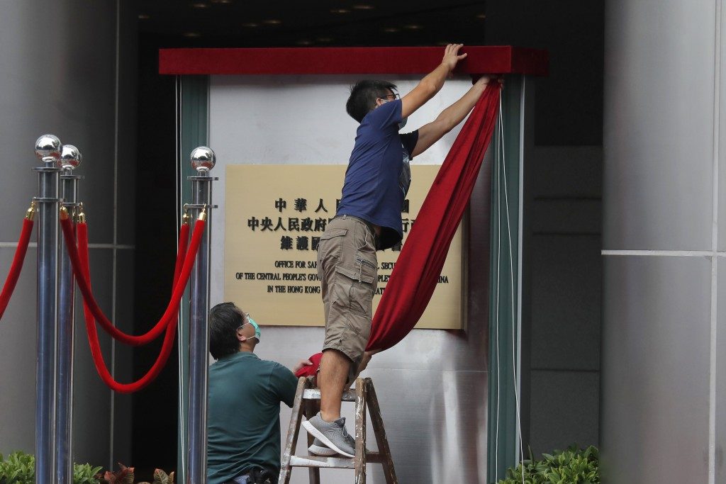 Workers take off a curtain after attend an opening ceremony for China's new Office for Safeguarding National Security in Hong Kong, Wednesday, July 8,...