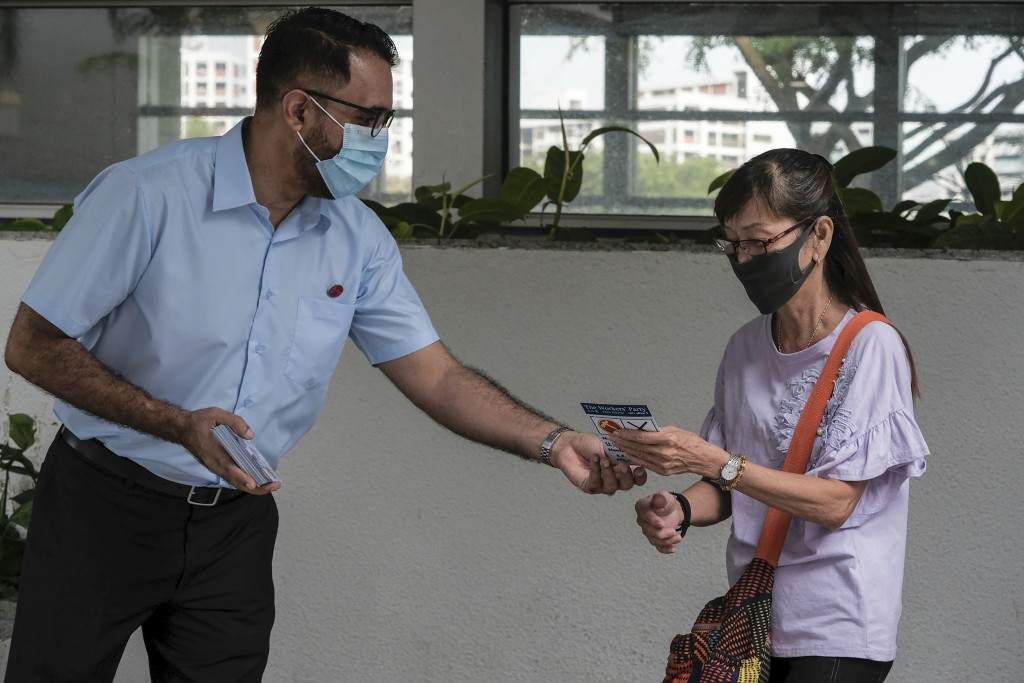 Workers' Party Secretary-General Pritam Singh gives a pamphlet to a woman outside the MRT station in Hougang during the final day of the election camp...