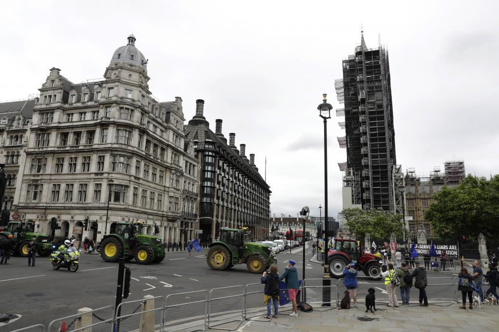 Farmers from the group Save British Farming drive tractors around Parliament Square, backdropped by the Houses of Parliament, at right, and the scaffo...