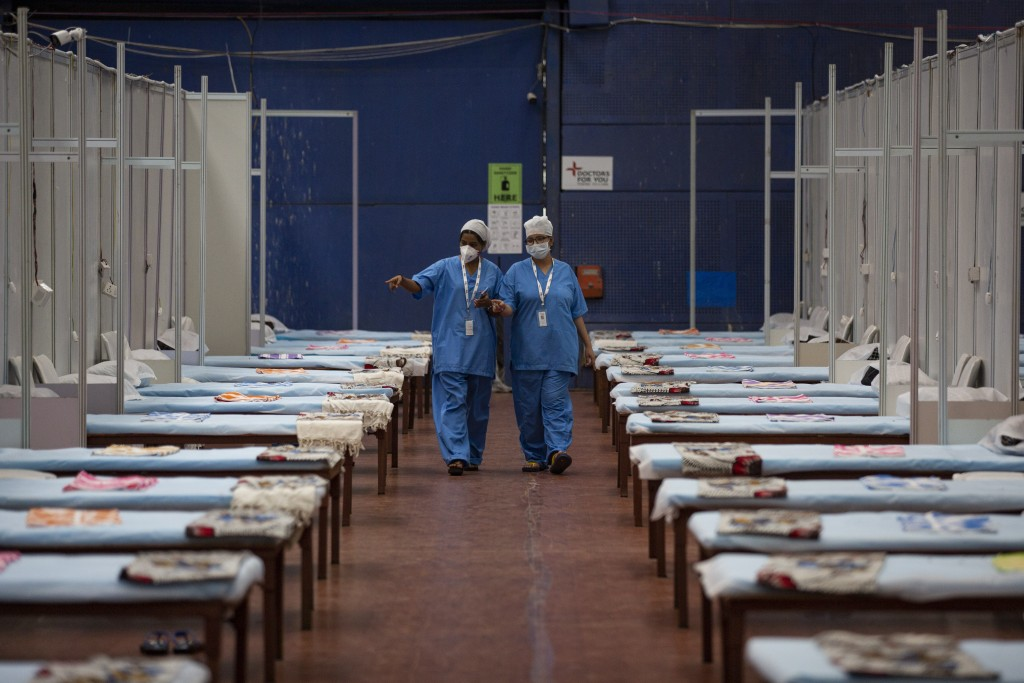 Medical staff walk past rows of beds at a makeshift COVID-19 care center at an indoor sports stadium after it was thrown open for patients in New Delh...