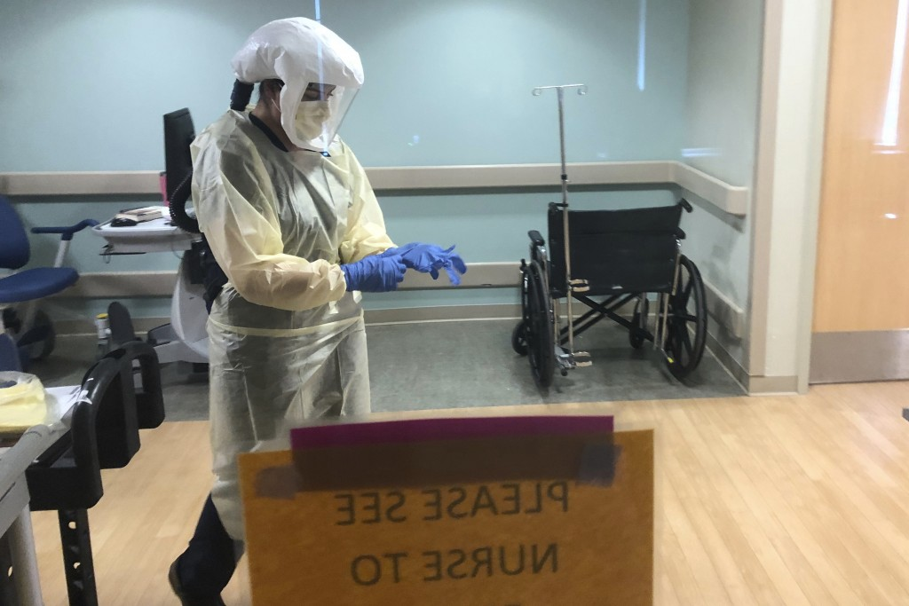 In this photo provided by the UPMC, Dr. Ruba Nicola, chairwoman of family medicine at UPMC East, adjusts her personal protective equipment at the UPMC...