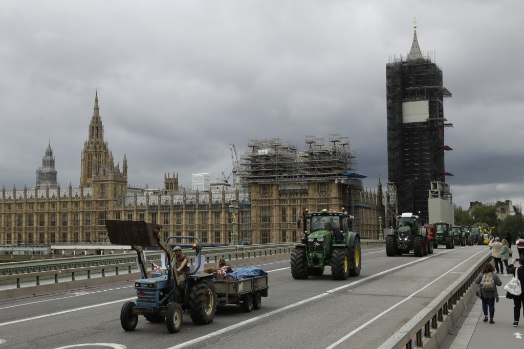 Farmers from the group Save British Farming drive tractors across Westminster Bridge, backdropped by the Houses of Parliament and the scaffolded Big B...