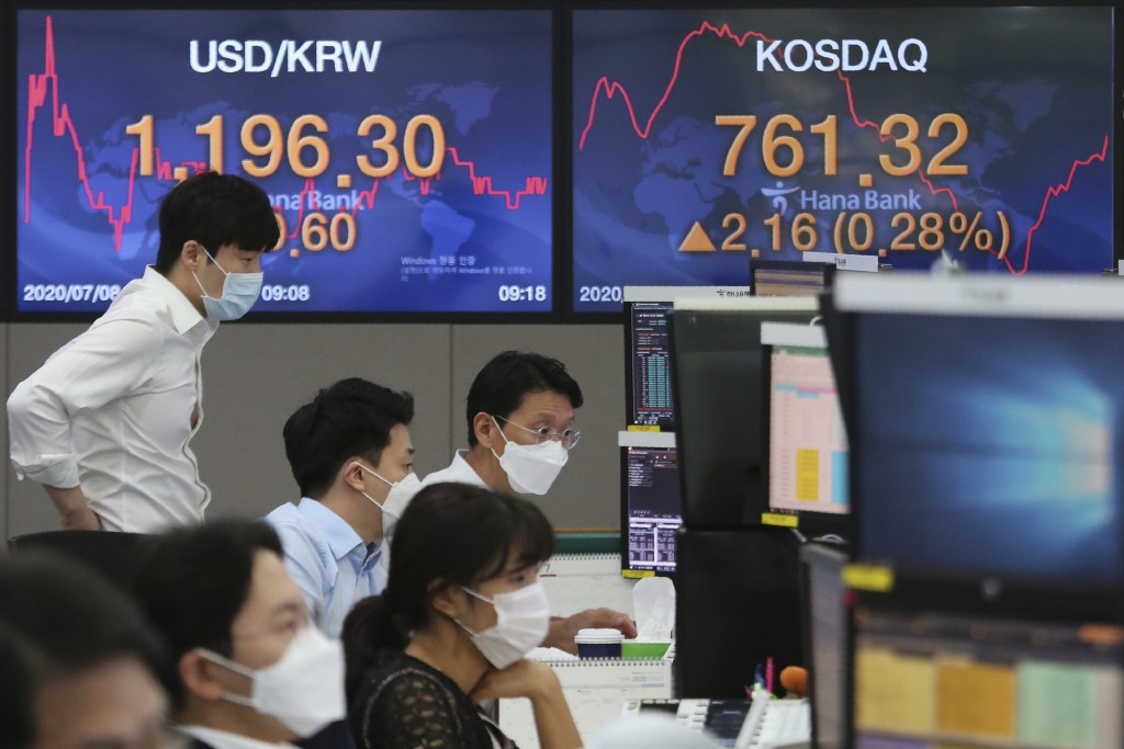 Currency traders watch monitors at the foreign exchange dealing room of the KEB Hana Bank headquarters in Seoul, South Korea, Wednesday, July 8, 2020....