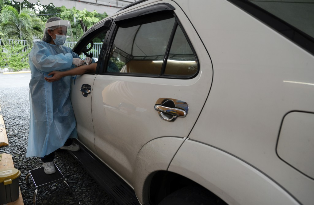 A health worker takes blood to perform an Enhanced Chemiluminescence Immunoassay (ECLIA) antibody test at a drive-thru COVID-19 testing facility at a ...