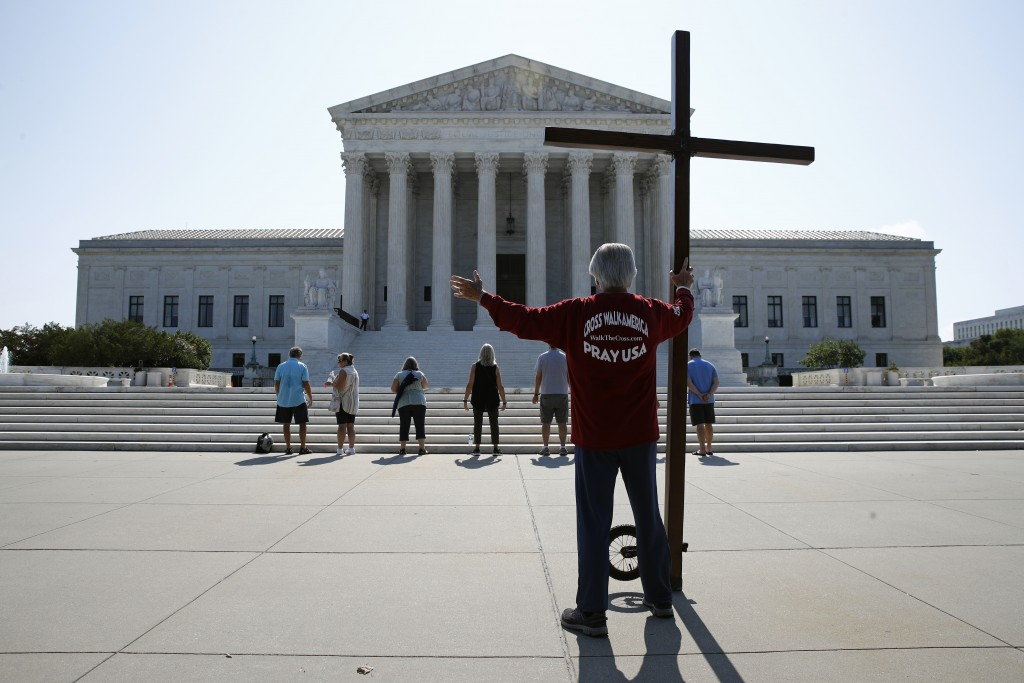 Tom Alexander holds a cross as he prays prior to rulings outside the Supreme Court on Capitol Hill in Washington, Wednesday, July 8, 2020.  The Suprem...