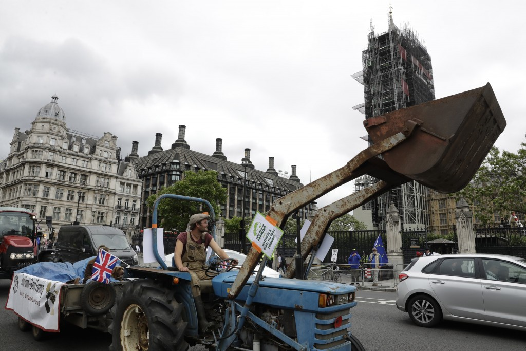 Farmers from the group Save British Farming drive tractors around Parliament Square, backdropped by the Houses of Parliament and the scaffolded Big Be...
