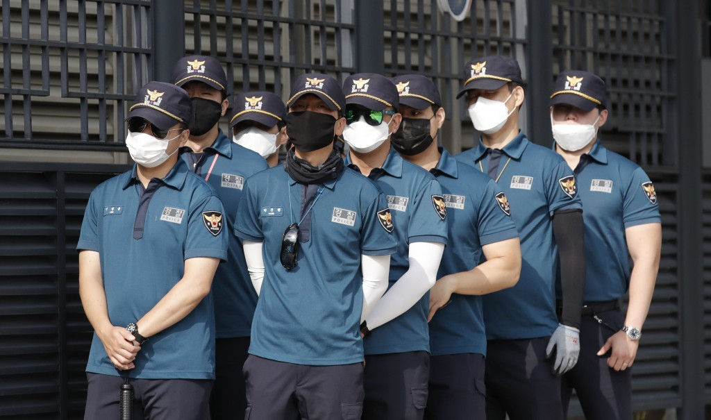 South Korean police officers wearing face masks to help protect against the spread of the new coronavirus, stand guard outside of Foreign Ministry in ...