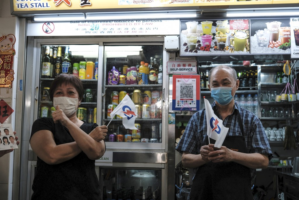 Shopkeepers at Bedok South market hold miniature flags of the People's Action Party during the final day of the election campaign Wednesday, July 8, 2...