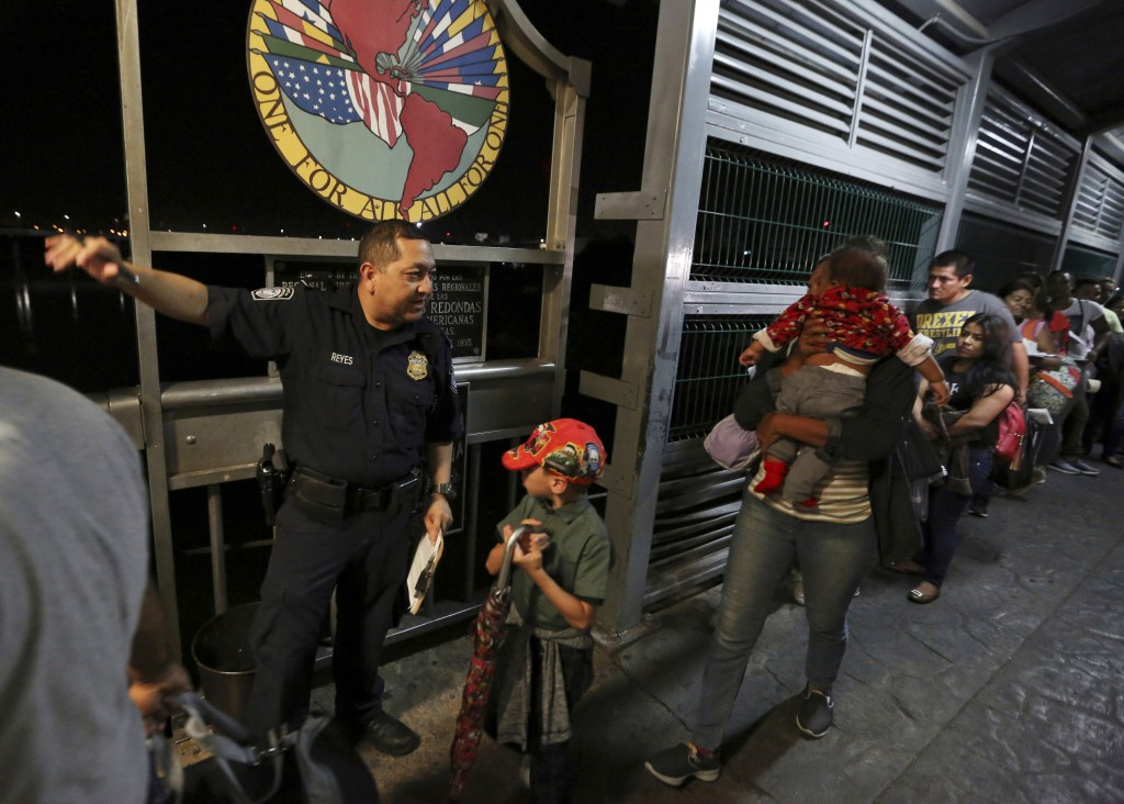 FILE - In this Sept. 17, 2019, file photo, a U.S. Customs and Border Protection officer gives instructions to migrants who are on their way to apply f...