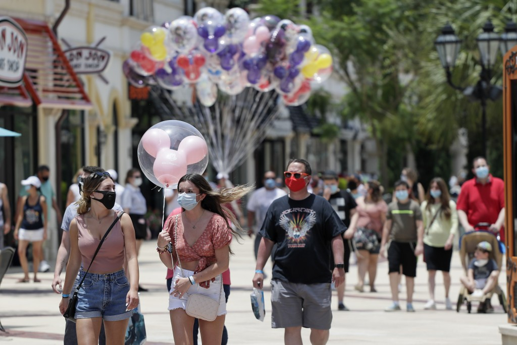 FILE - In this June 16, 2020, file photo, guests required to wear masks because of the coronavirus stroll through the Disney Springs shopping, dining ...
