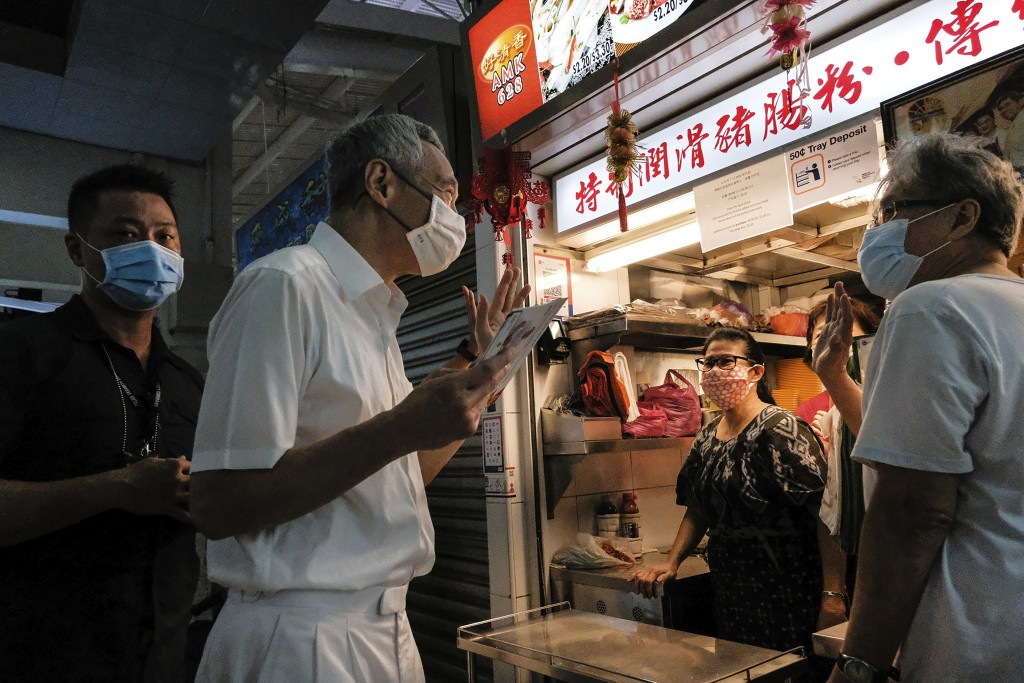 Singapore Prime Minister and Secretary-General of the People's Action Party Lee Hsien Loong, second left, wears a face mask while talking to food vend...
