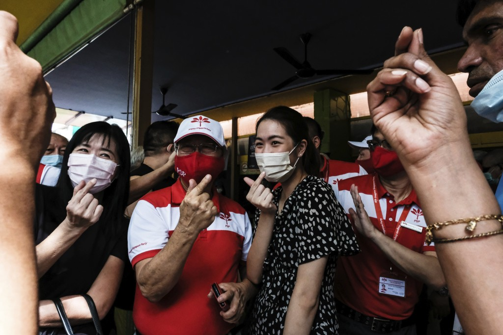 Progress Singapore Party Secretary-General Dr Tan Cheng Bock, center left, wears a face mask while making a heart hand gesture with female supporters ...