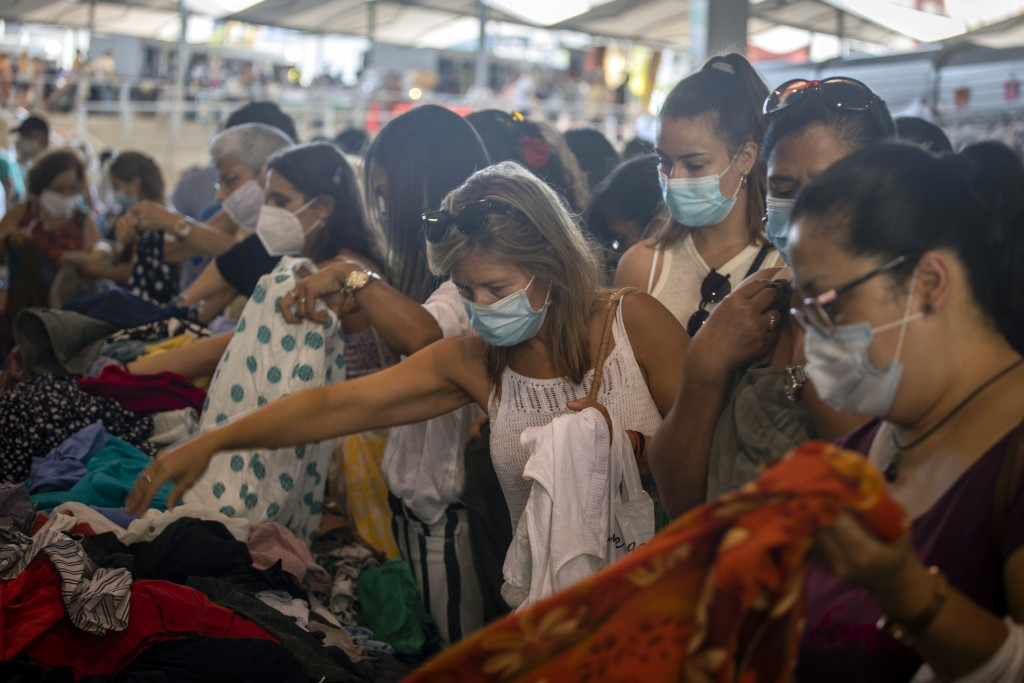 Customers wearing face masks buy clothes for one euro at a stall in a market in Barcelona on Wednesday, July 8, 2020. Spain's northeastern Catalonia r...