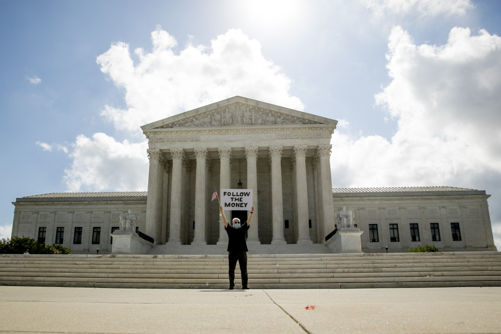 "Bill Christeson holds up a sign that reads ""Follow the Money"" outside the Supreme Court, Thursday, July 9, 2020, in Washington. (AP Photo/Andrew Harni..."