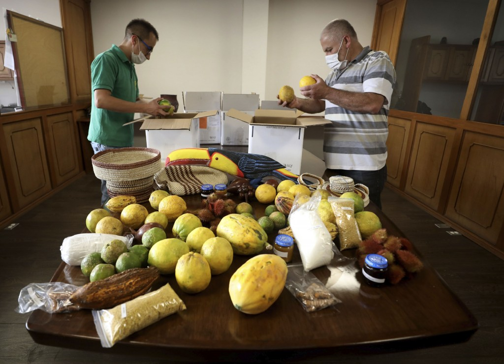 Workers pack crafts and fruits from the Amazon on a box before 'The Harvest Amazonian Barter' will deliver to people who subscribe to the service in B...
