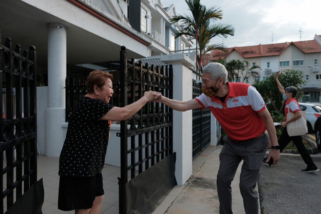 Lee Hsien Yang, the estranged brother of Singapore Prime Minister Lee Hsien Loong, wears a face mask while doing a fist bump with a female resident at...