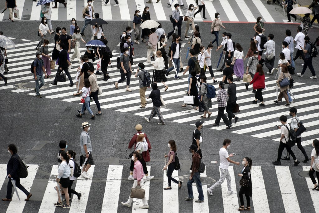 People wearing a protective face mask to help curb the spread of the coronavirus walk at Shibuya pedestrian crossing Thursday, July 9, 2020, in Tokyo....