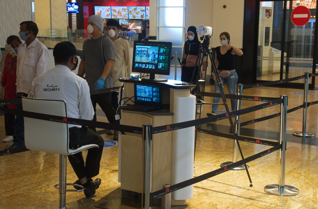 FILE - In this May 27, 2020, file photo, a security guard watches an infrared scanner monitoring incoming customers for fevers at Mall of the Emirates...