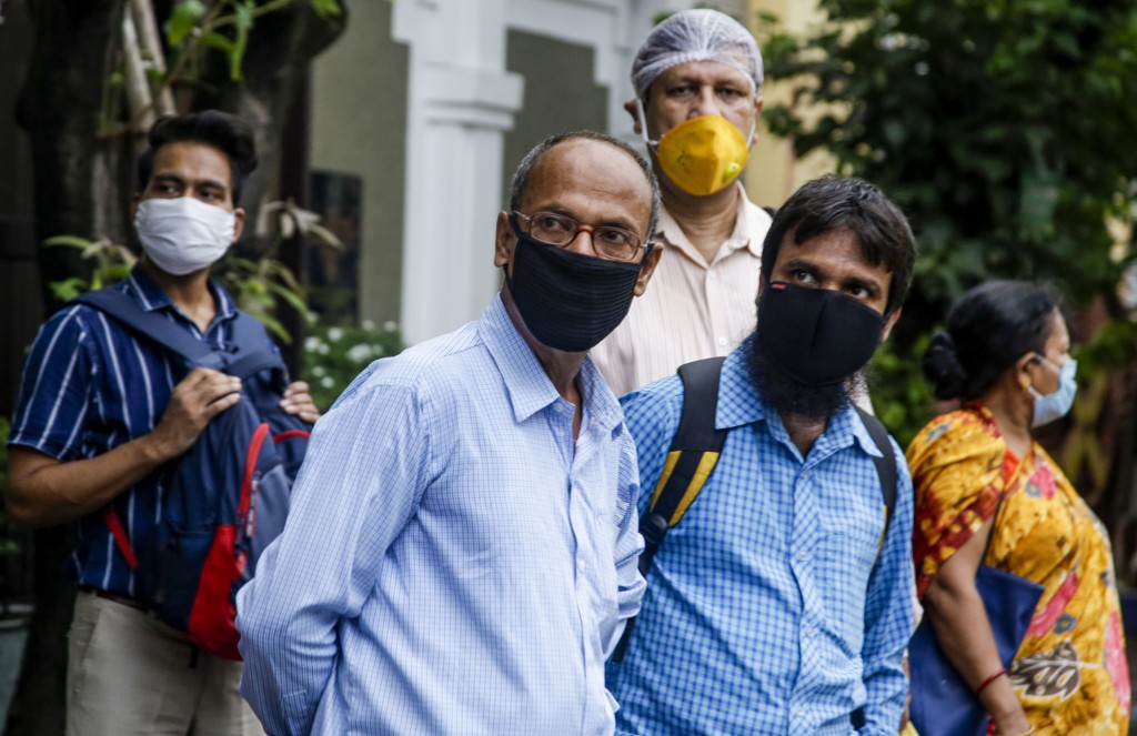 Commuters with face mask as a precaution against the coronavirus wait for a bus in Kolkata, India, Thursday, July 9, 2020. India has overtaken Russia ...