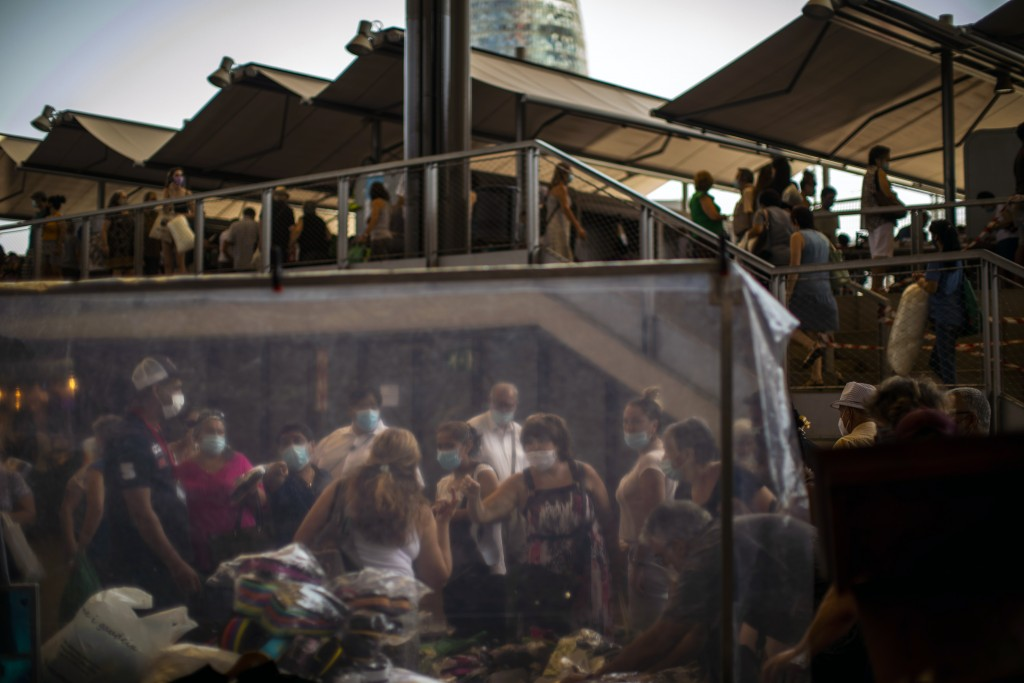 Customers wearing face masks buy sandals at a market in Barcelona on Wednesday, July 8, 2020. Spain's northeastern Catalonia region will make mandator...