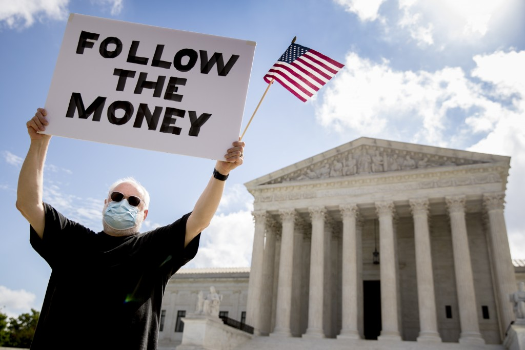 """Bill Christeson holds up a sign that reads """"Follow the Money"""" outside the Supreme Court, Thursday, July 9, 2020, in Washington. The Supreme Court rule..."""