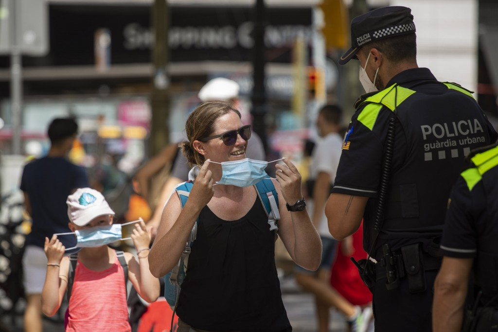 Catalonian police officers ask at a woman to wear a face mask, in Las Ramblas of Barcelona, Spain, Thursday, July 9, 2020. Authorities in northeast Sp...
