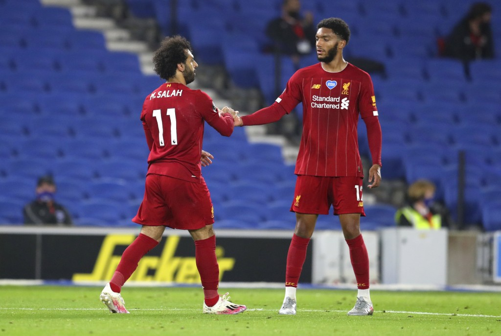 Liverpool's Mohamed Salah, left, is congratulated by teammate Joe Gomez after scoring his team's third goal during the English Premier League soccer m...