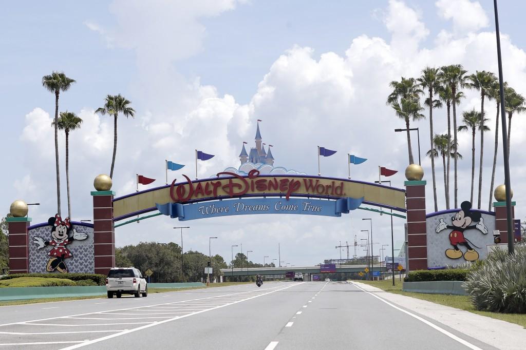 Cars drive under a sign greeting visitors near the entrance to Walt Disney World, Thursday, July 2, 2020, in Lake Buena Vista, Fla. Despite a huge sur...