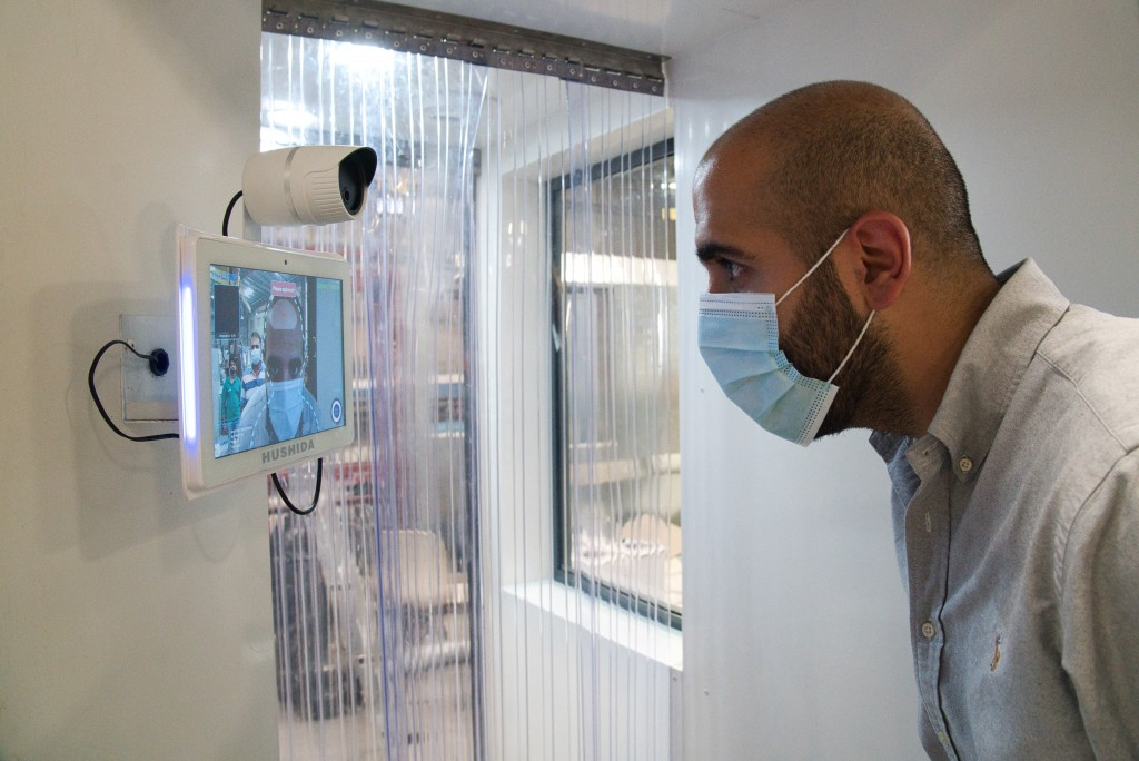 FILE - In this April 27, 2020, file, photo, a worker examines a gate system made by Guard ME that conducts temperature checks and fogs disinfectants o...