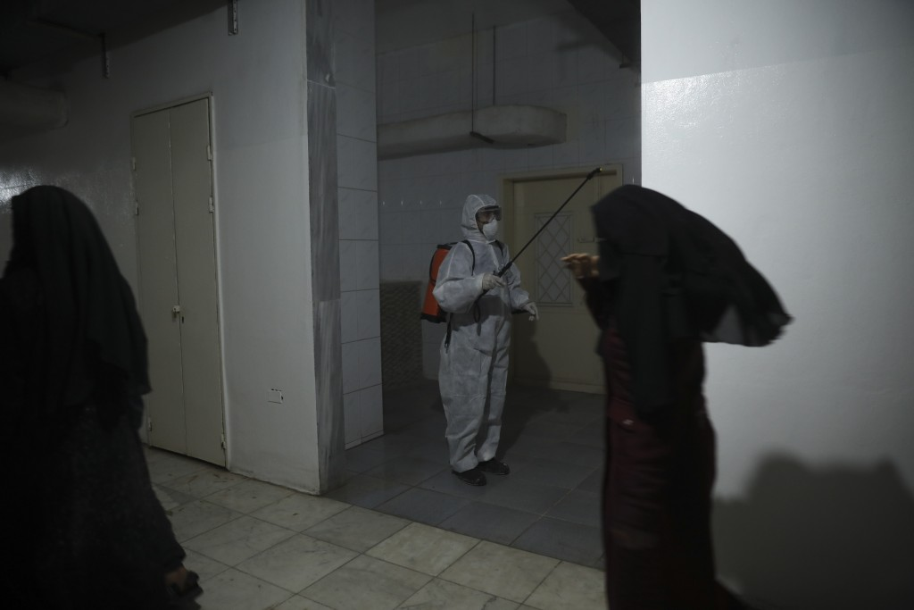 FILE - In this March 19, 2020 file photo, a member of a humanitarian aid agency disinfects inside Ibn Sina Hospital as prevention against the coronavi...