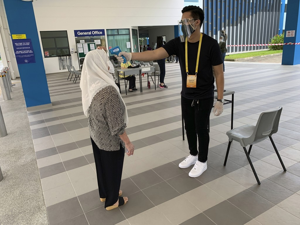 A voter, left, wearing a face mask has her temperature checked with a thermal scanner at the Dunearn Secondary School polling station in Singapore Fri...