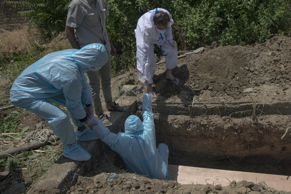 A man is helped out by others after burying the body of a relative who died of COVID-19, at a cemetery in Srinagar, Indian controlled Kashmir, Friday,...