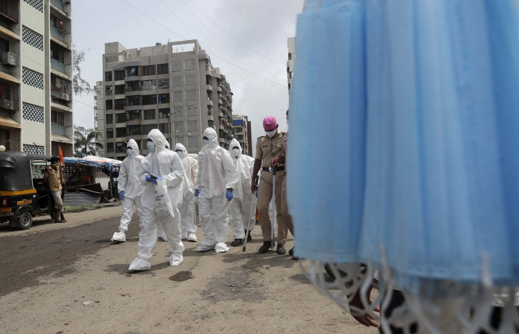 Health workers escorted by policemen arrive to screen people for COVID-19 symptoms at a slum in Mumbai, India, Friday, July 10, 2020. India has overta...