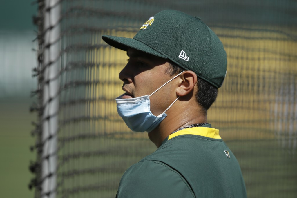 Oakland Athletics pitcher Sean Manaea wears a mask, but slung low, during baseball practice Thursday, July 9, 2020, in Oakland, Calif. (AP Photo/Ben M...