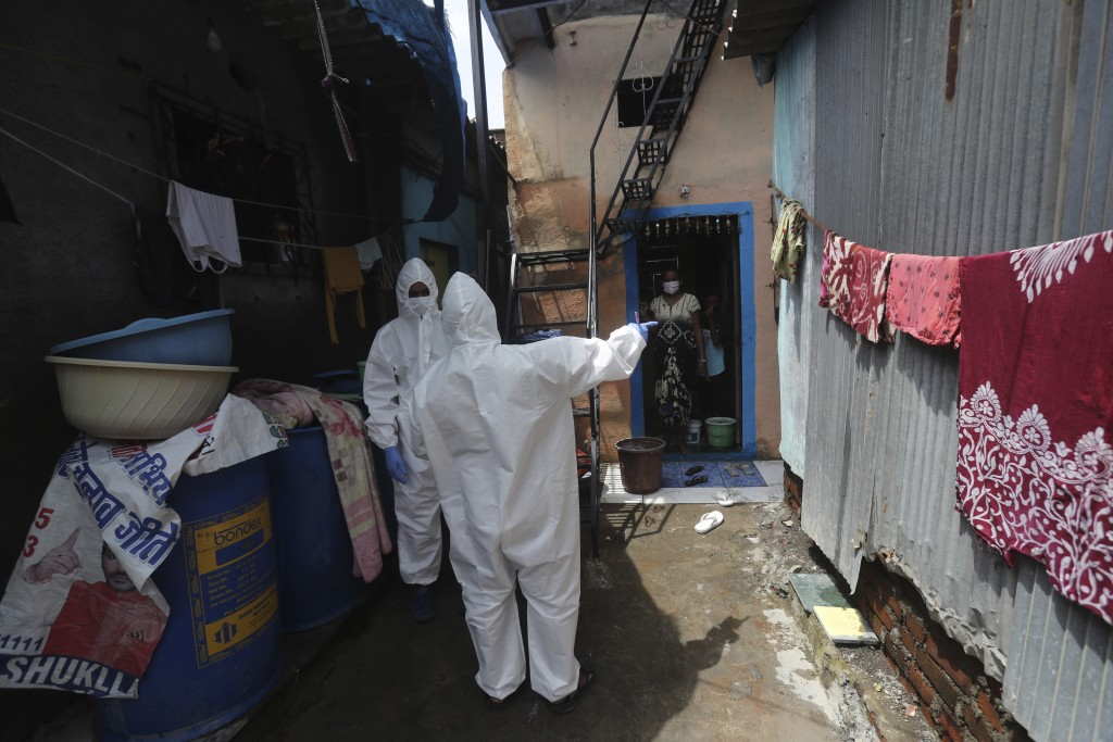 Health workers walk to screen people for COVID-19 symptoms at a slum in Mumbai, India, Friday, July 10, 2020. India has overtaken Russia to become the...