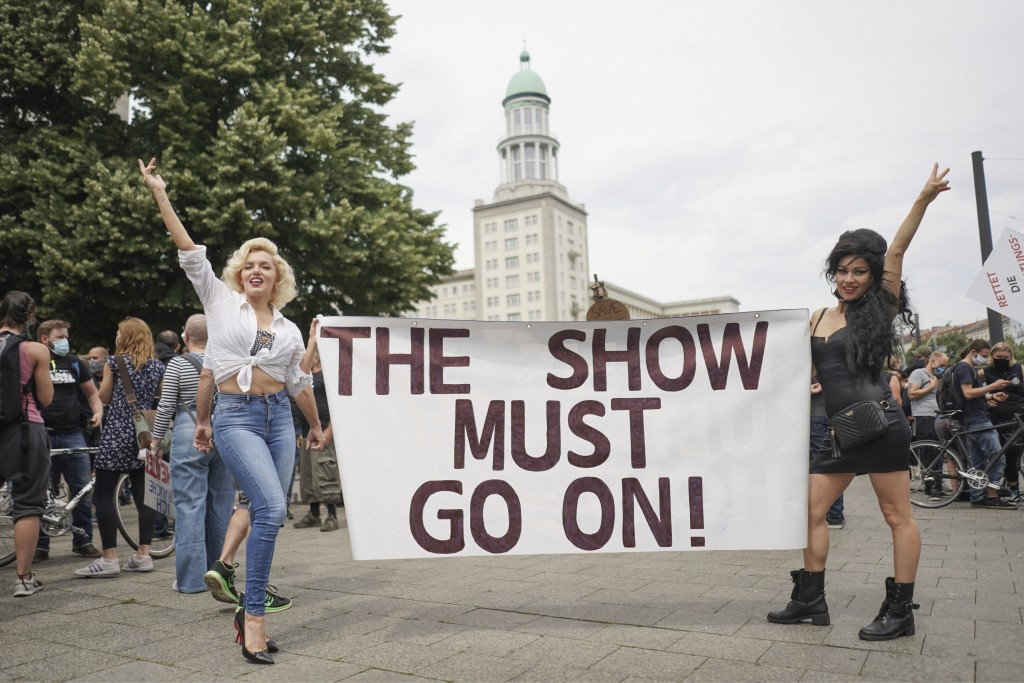 """Suzy and Rachel, two performers from the Estrel Hotel looking like Marilyn Monroe and Amy Winehouse, hold a poster with the words """"The Show must go on..."""