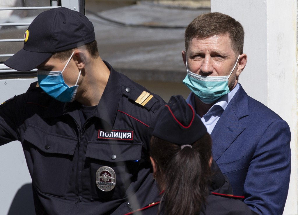A governor of the Khabarovsk region along the border with China, Sergei Furgal, right, is escorted from a court room in Moscow, Russia, Friday, July 1...